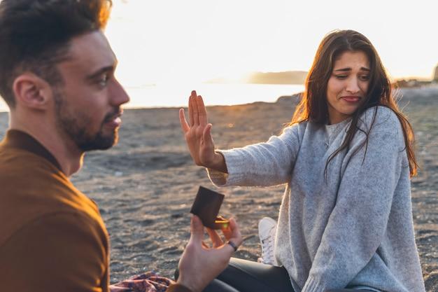 Donna che rifiuta la proposta di matrimonio sulla riva del mare Foto Gratuite
