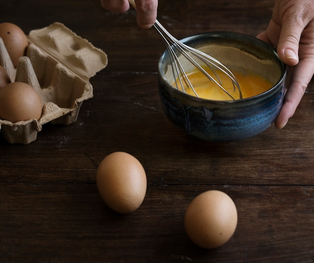Donna che sbatte l'idea di ricetta di fotografia dell'alimento delle uova Foto Premium