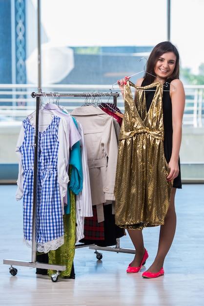 Donna che sceglie i vestiti nel negozio Foto Premium