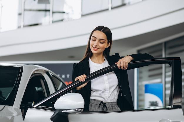 Donna che sceglie un'automobile in una sala d'esposizione dell'automobile Foto Gratuite