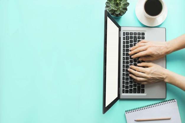 Donna che scrive dal computer portatile sul blu dell'ufficio. sfondo di copyspace Foto Premium