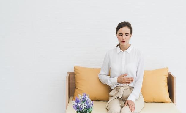 Donna che sente dolore addominale mentre era seduto sul divano del salotto Foto Premium