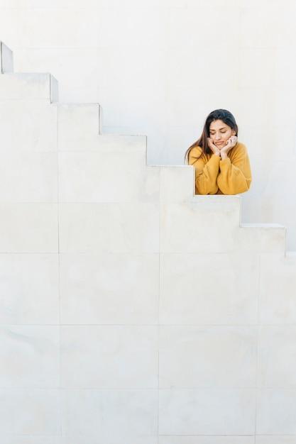 Donna che si appoggia sui gradini bianchi guardando lontano Foto Gratuite