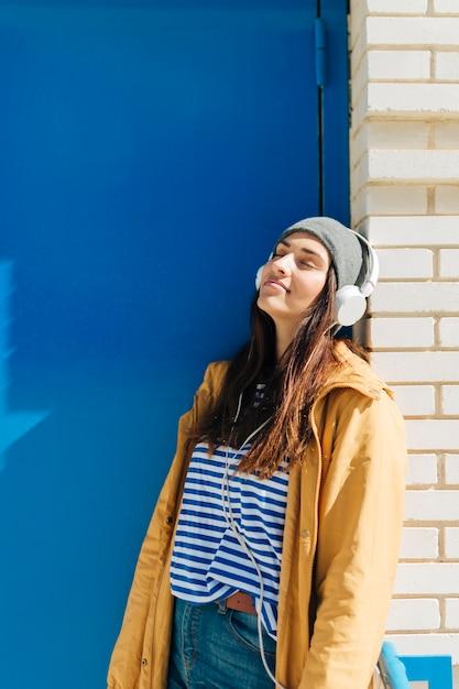 Donna che si appoggia sulla parete indossando le cuffie con gli occhi chiusi Foto Gratuite