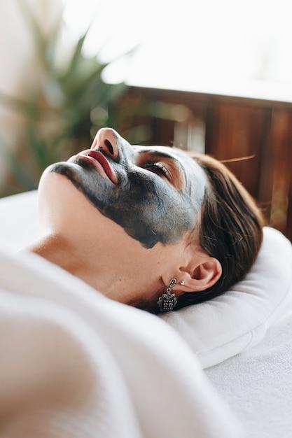 Donna che si distende con una maschera facciale presso la spa Foto Gratuite
