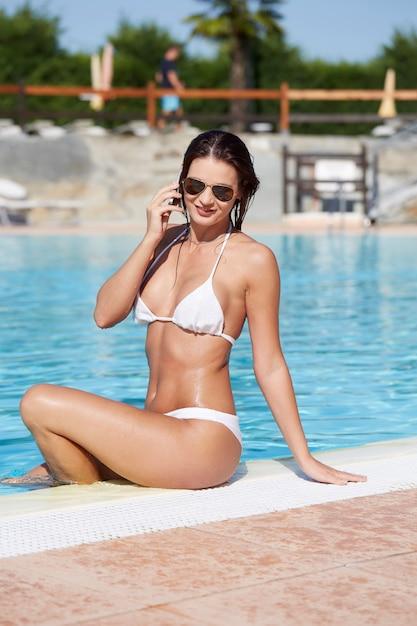 Donna che si distende in piscina Foto Premium