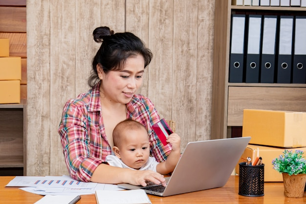 Donna che si prende cura del suo bambino mentre si lavora in ufficio Foto Premium