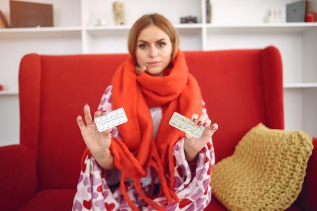 Donna che si siede a casa con il raffreddore e che prende le pillole Foto Gratuite