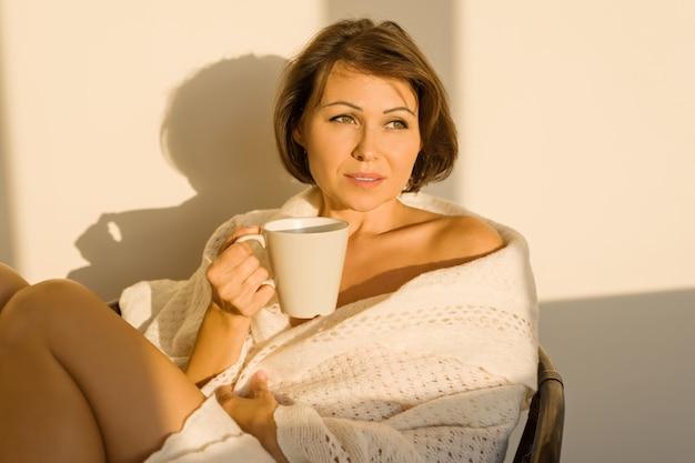 Donna che si siede a casa su una sedia in coperta lavorata a maglia di lana Foto Premium