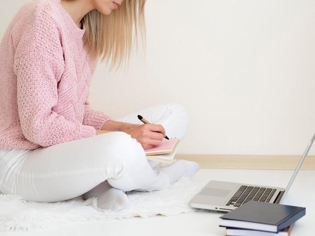 Donna che si siede a letto e che scrive informazioni dal computer portatile Foto Gratuite