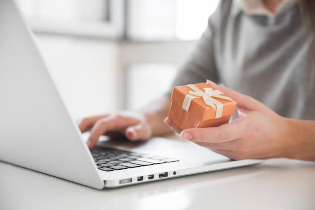 Donna che si siede al tavolo con scatola regalo e portatile Foto Gratuite