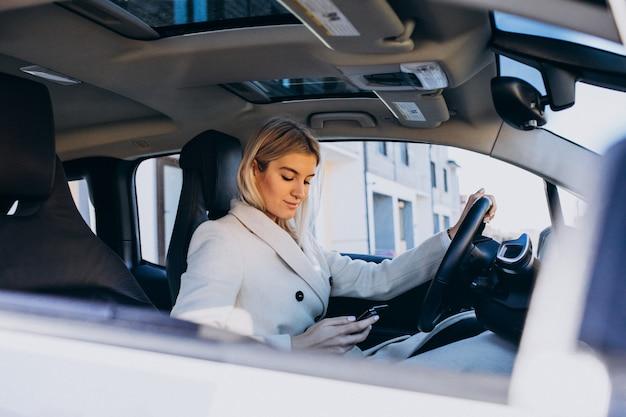 Donna che si siede all'interno dell'elettro automobile durante la ricarica Foto Gratuite