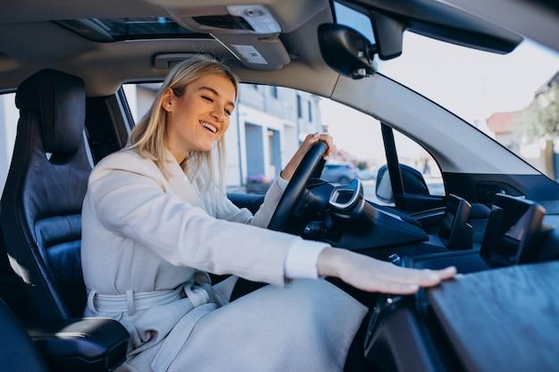 Donna che si siede all'interno dell'elettro automobile mentre si carica Foto Gratuite