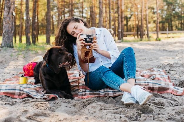 Donna che si siede con il suo cane in natura Foto Gratuite