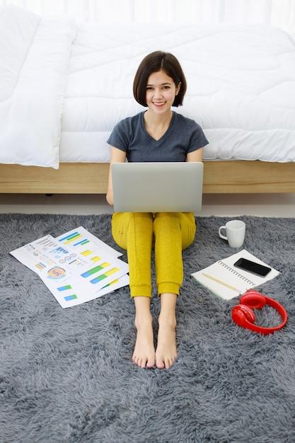 Donna che si siede e che utilizza computer nella camera da letto Foto Premium
