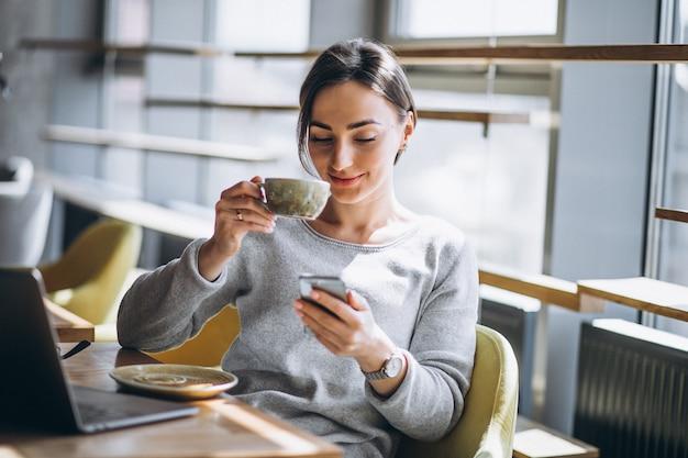 Donna che si siede in un caffè bevendo caffè e lavorando su un computer Foto Gratuite