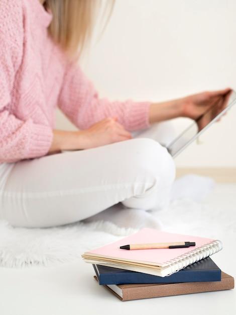 Donna che si siede nel letto e che per mezzo della compressa digitale Foto Gratuite