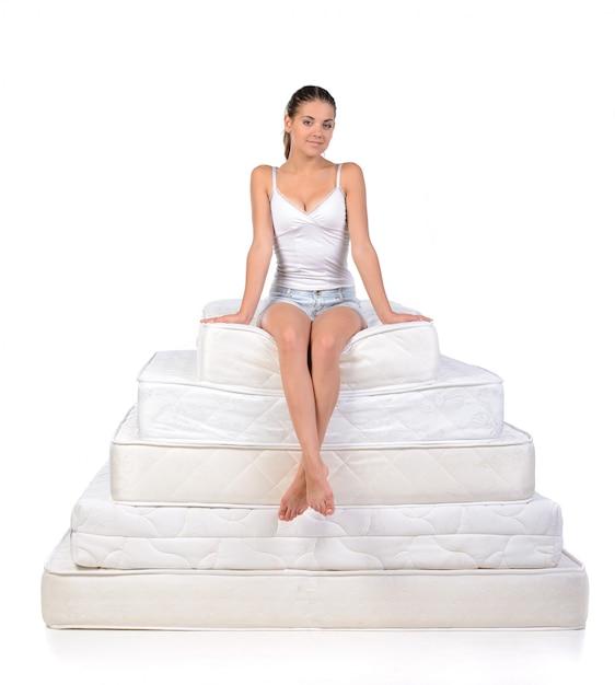 Donna che si siede su molti materassi. Foto Premium