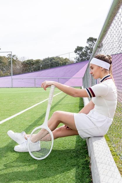 Donna che si siede su un campo da tennis Foto Gratuite