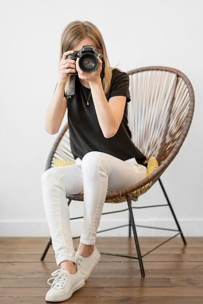 Donna che si siede su un colpo lungo della sedia Foto Gratuite