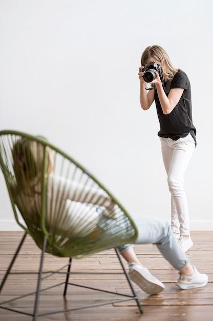 Donna che si siede su una sedia e sul fotografo possibilità remota Foto Gratuite