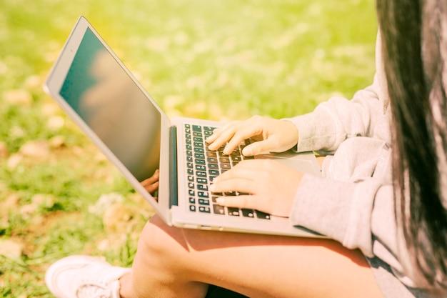 Donna che si siede sull'erba verde e che lavora in computer portatile Foto Gratuite