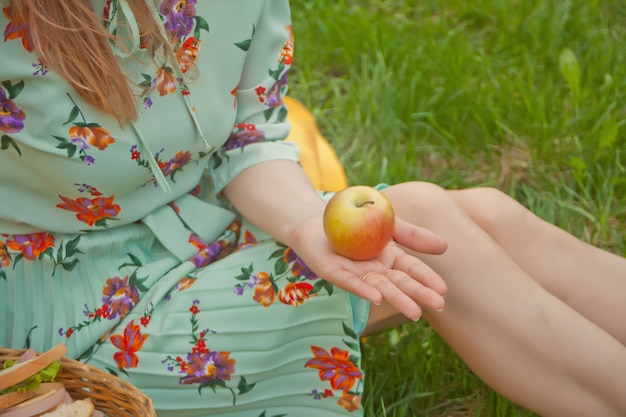 Donna che si siede sulla copertina gialla su un'erba verde e che tiene mela in una mano. Foto Premium