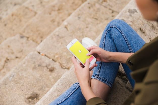 Donna che si siede sulla scala usando app snapchat su smartphone Foto Gratuite