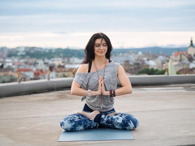 Donna che si siede sulla stuoia di yoga con gli occhi chiusi durante la meditazione Foto Premium