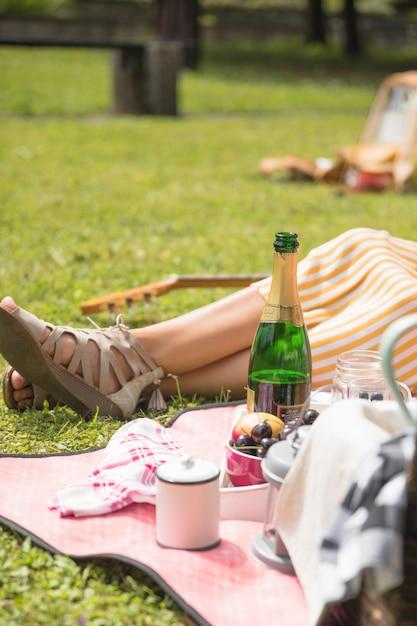 Donna che si siede vicino allo spuntino sul picnic Foto Gratuite