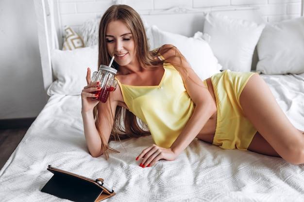 Donna che si trova sul letto facendo uso della compressa e bevendo Foto Premium