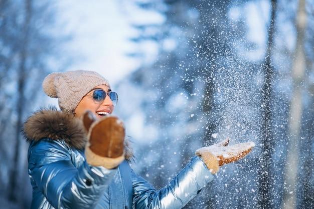 Donna che soffia neve dai guanti Foto Gratuite