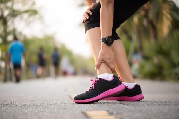 Donna che soffre di una lesione alla caviglia durante l'allenamento. esecuzione del concetto di infortunio Foto Premium