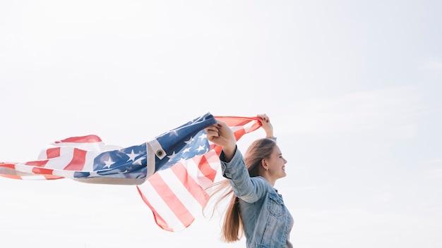 Donna che sorride e che tiene ampia bandiera americana d'ondeggiamento su in cielo Foto Gratuite