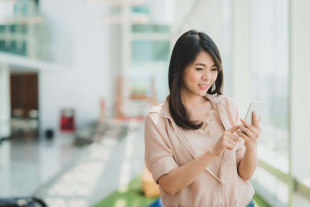 Donna che sorride mentre utilizzando smartphone nell'ufficio moderno Foto Premium