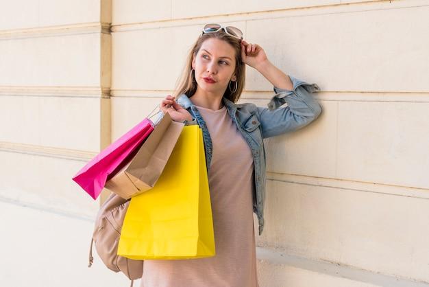 Donna che sta con i sacchetti della spesa luminosi alla parete leggera Foto Gratuite