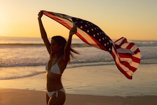 Donna che sta con la bandiera americana d'ondeggiamento sulla spiaggia Foto Gratuite