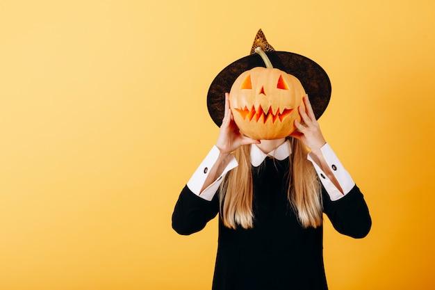 Donna che sta contro una zucca gialla della tenuta e che nasconde il suo fronte Foto Premium