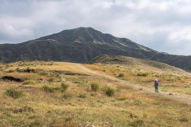 Donna che sta nel lanscape verde con la montagna aso, kusasenri, kumamoto, kyushu Foto Premium