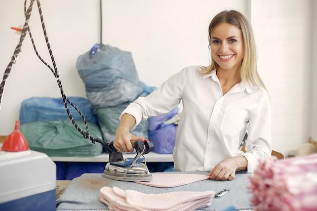 Donna che sta nella fabbrica con un filo Foto Gratuite