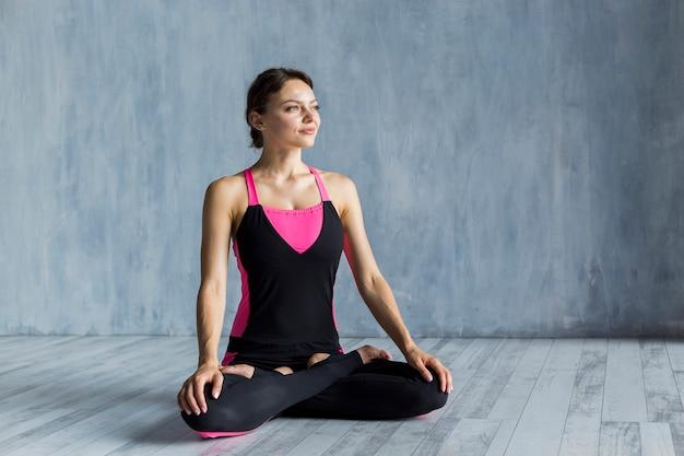 Donna che sta nello yogapose del loto mentre guardando da parte Foto Gratuite