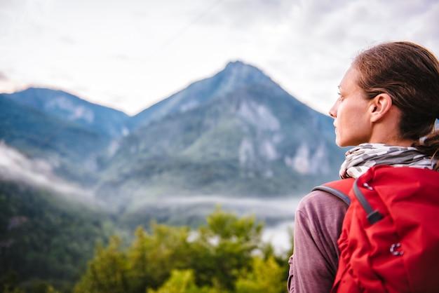 Donna che sta sulla montagna e che guarda lateralmente Foto Premium
