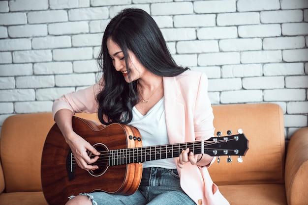 Donna che suona la chitarra sul divano Foto Premium
