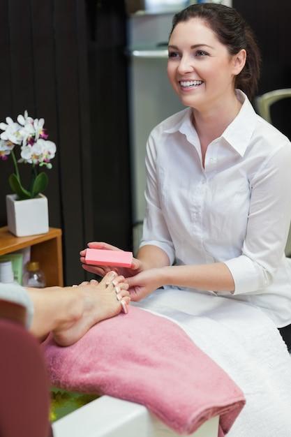 Donna che tampona le unghie dei piedi al centro benessere Foto Premium