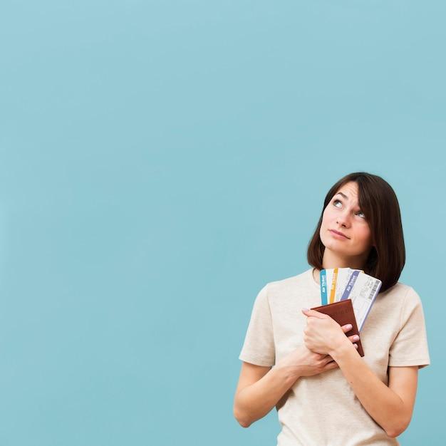 Donna che tiene alcuni biglietti di aeroplano con lo spazio della copia Foto Gratuite