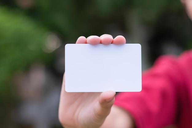 Donna che tiene biglietto da visita bianco su sfondo naturale bokeh Foto Premium