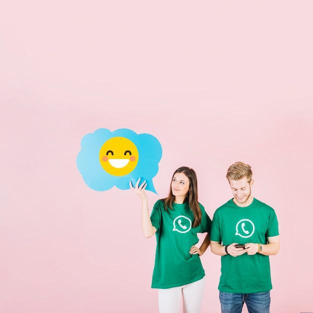 Donna che tiene fumetto blu con ridere emoji vicino uomo tramite cellulare Foto Gratuite