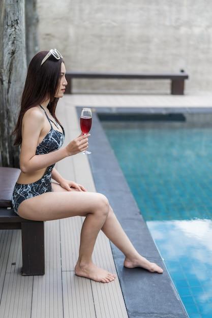 Donna che tiene il bicchiere di vino in piscina Foto Premium