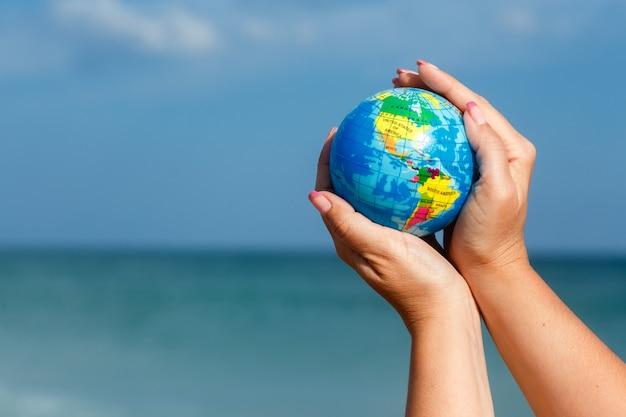 Donna che tiene il globo della terra su uno sfondo del mare. Foto Premium