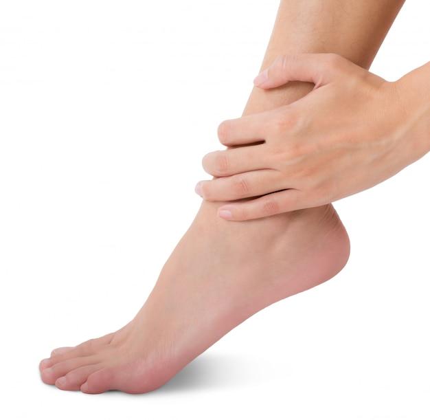 Donna che tiene il suo piede e che massaggia caviglia nell'area di dolore isolata su bianco Foto Premium